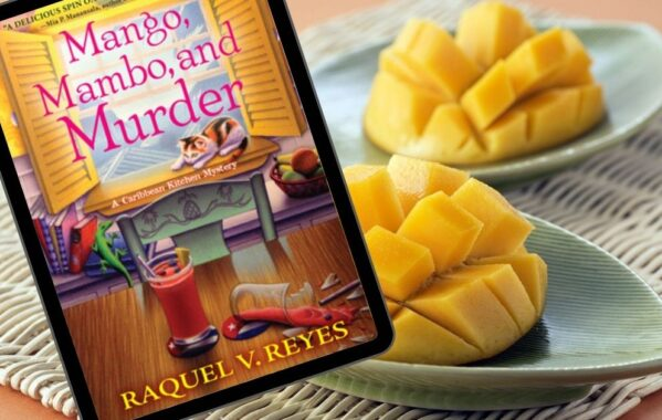 The book Mango, Mambo, and Murder in front of chopped mangoes